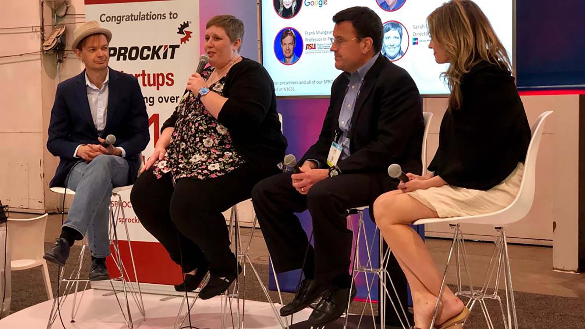 a panel with four people sitting in chairs