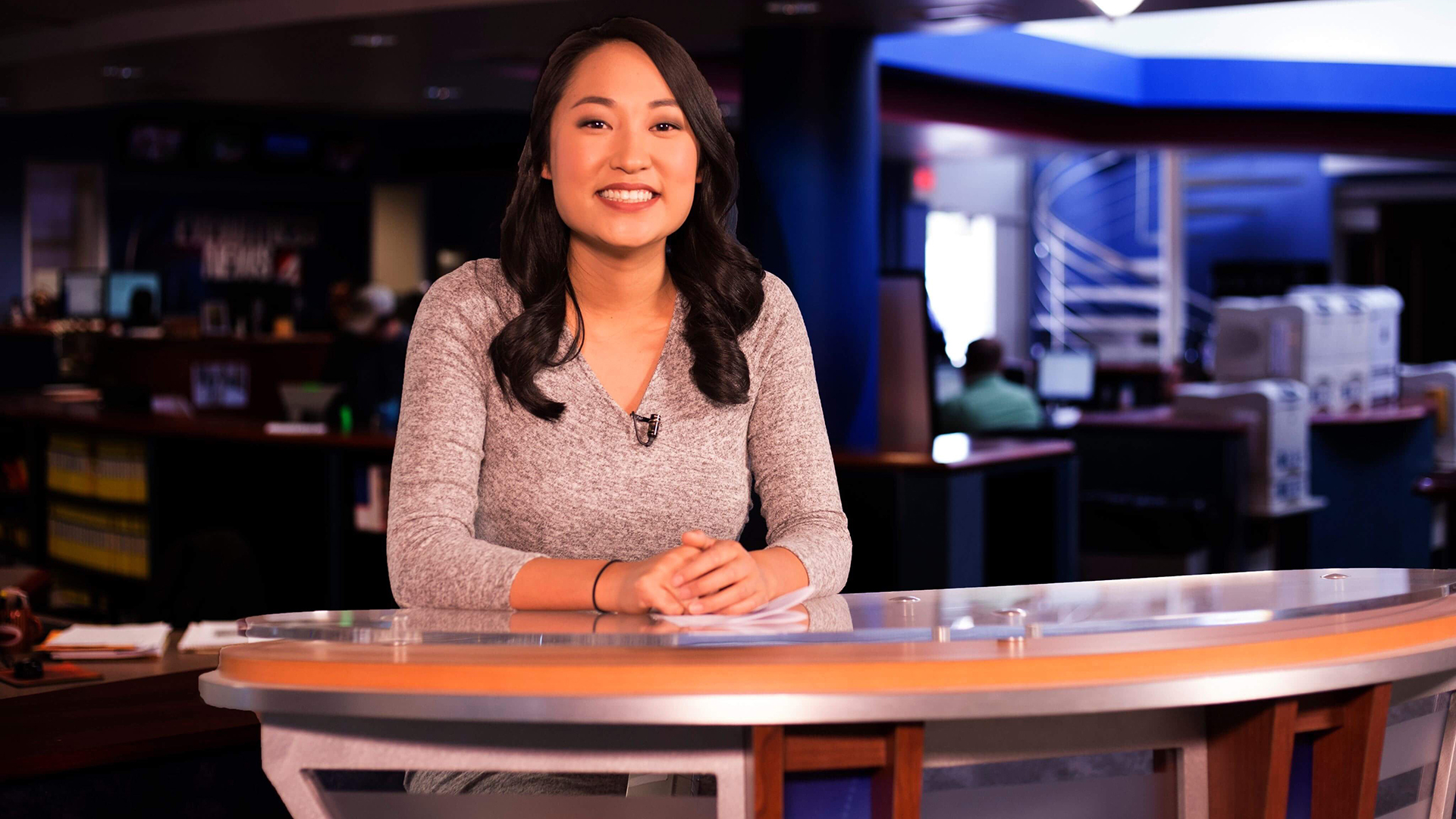 woman leaning on anchor desk