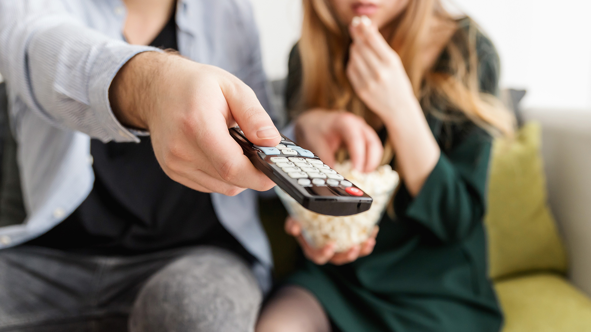 couple with remote control looking at TV