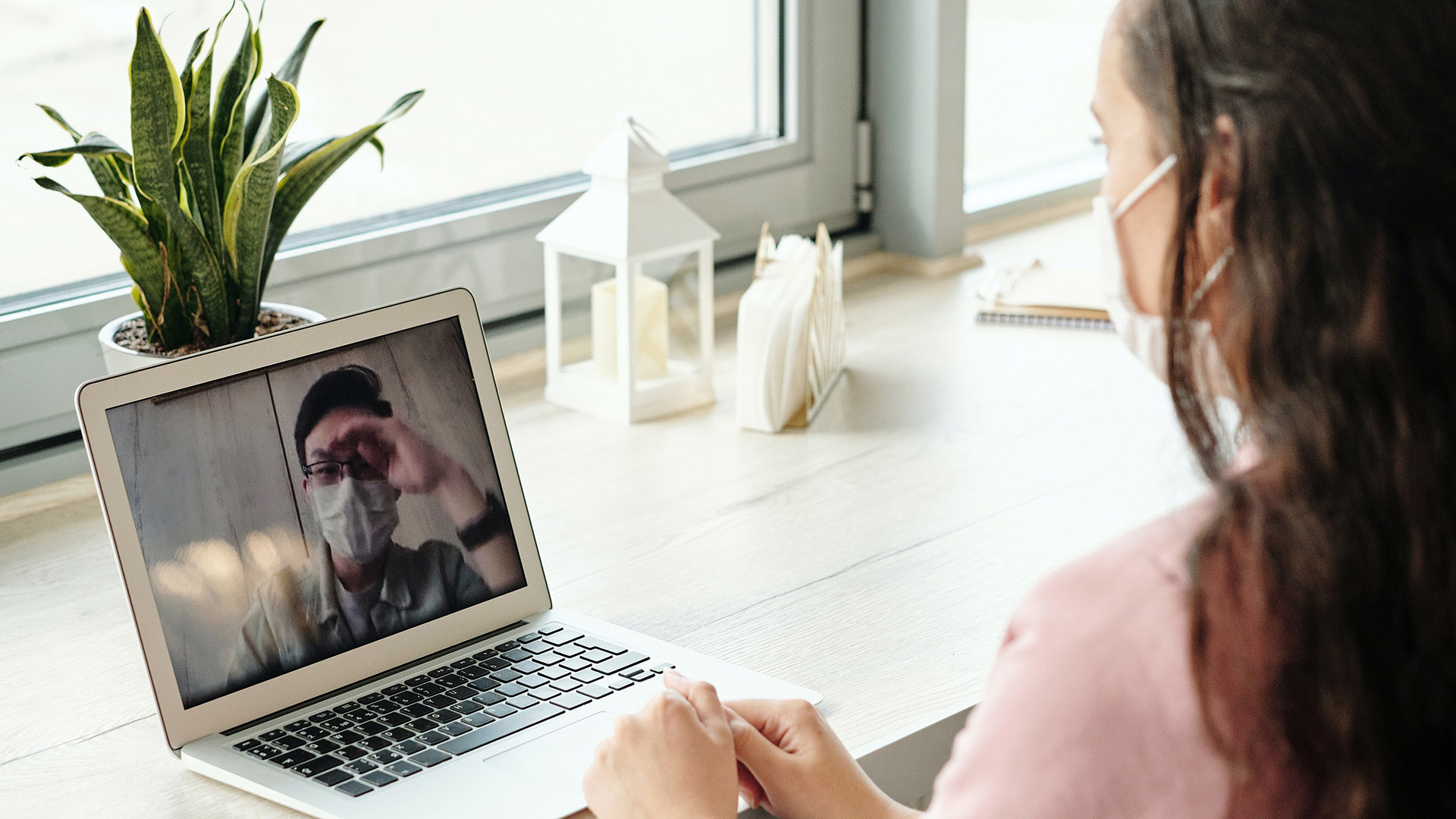 woman with face mask looking at laptop computer