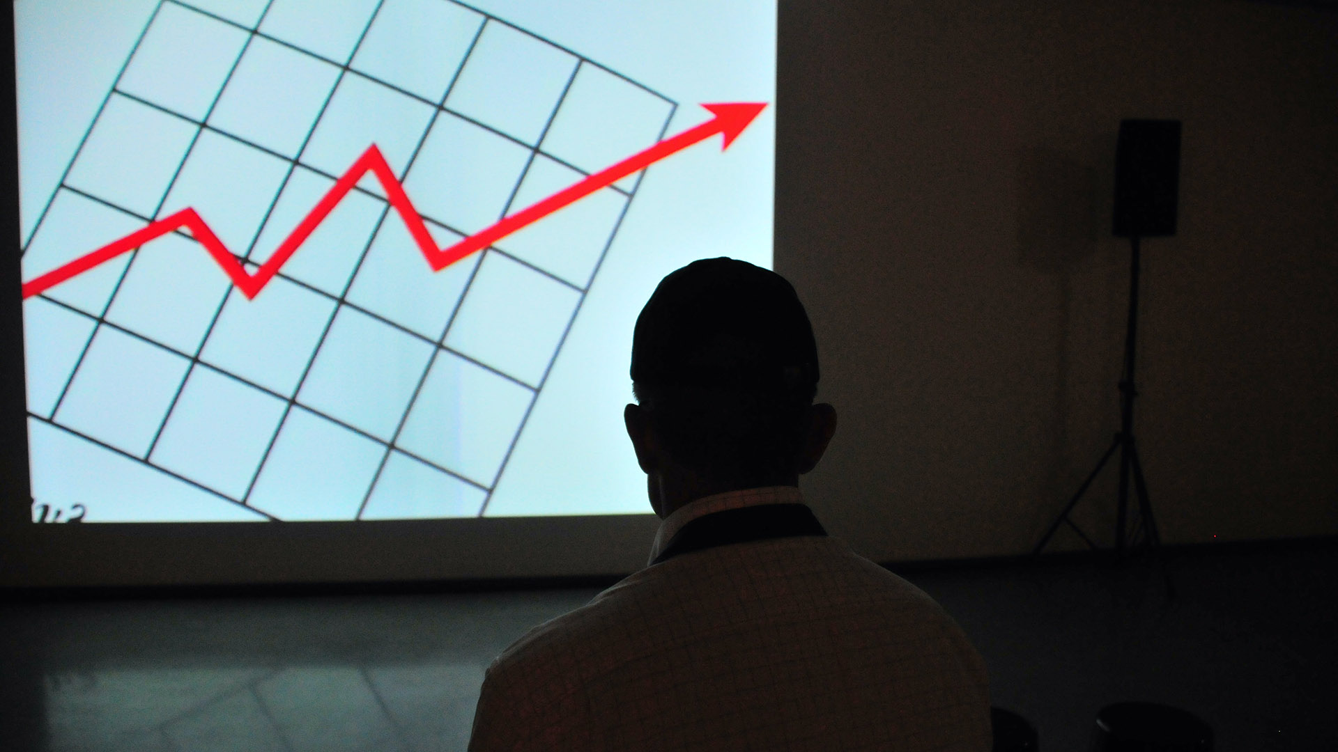 man looking at chart with upwards arrow