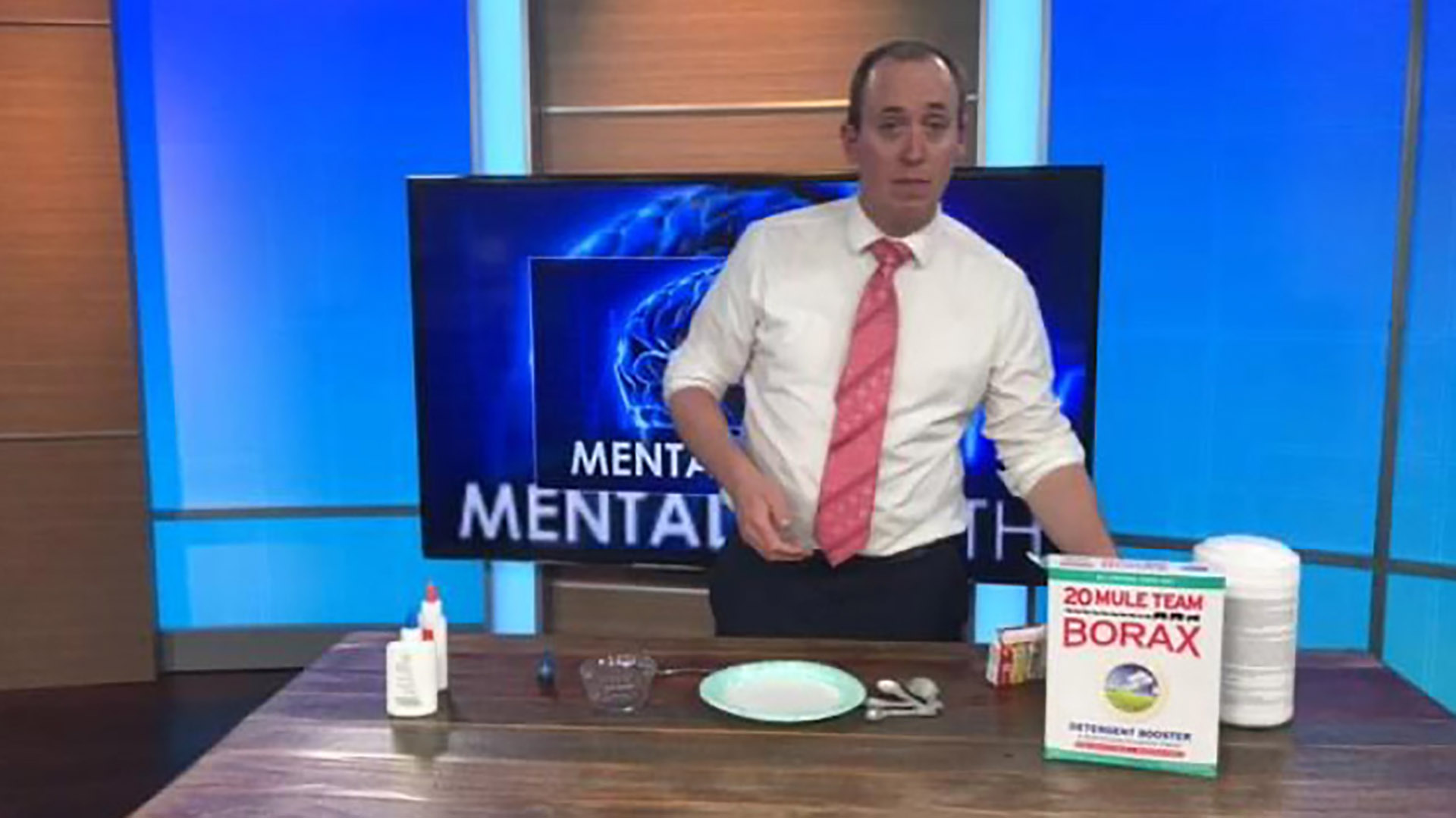 Meteorologist Mark Holley conducting a science experiment on a table