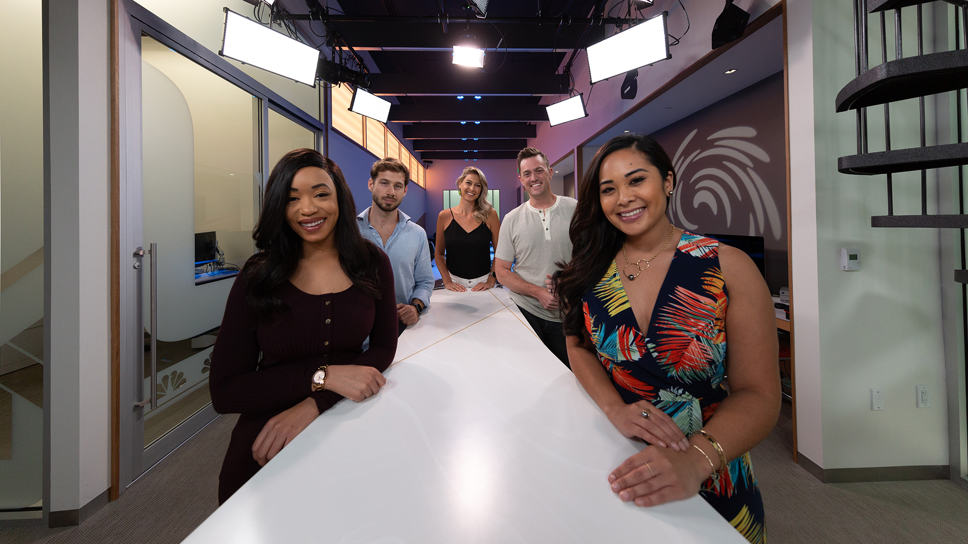 five diverse anchors standing around a desk