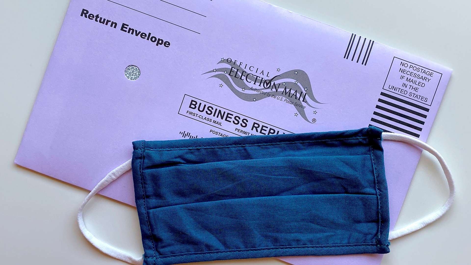 mail-in ballot with blue face mask over it
