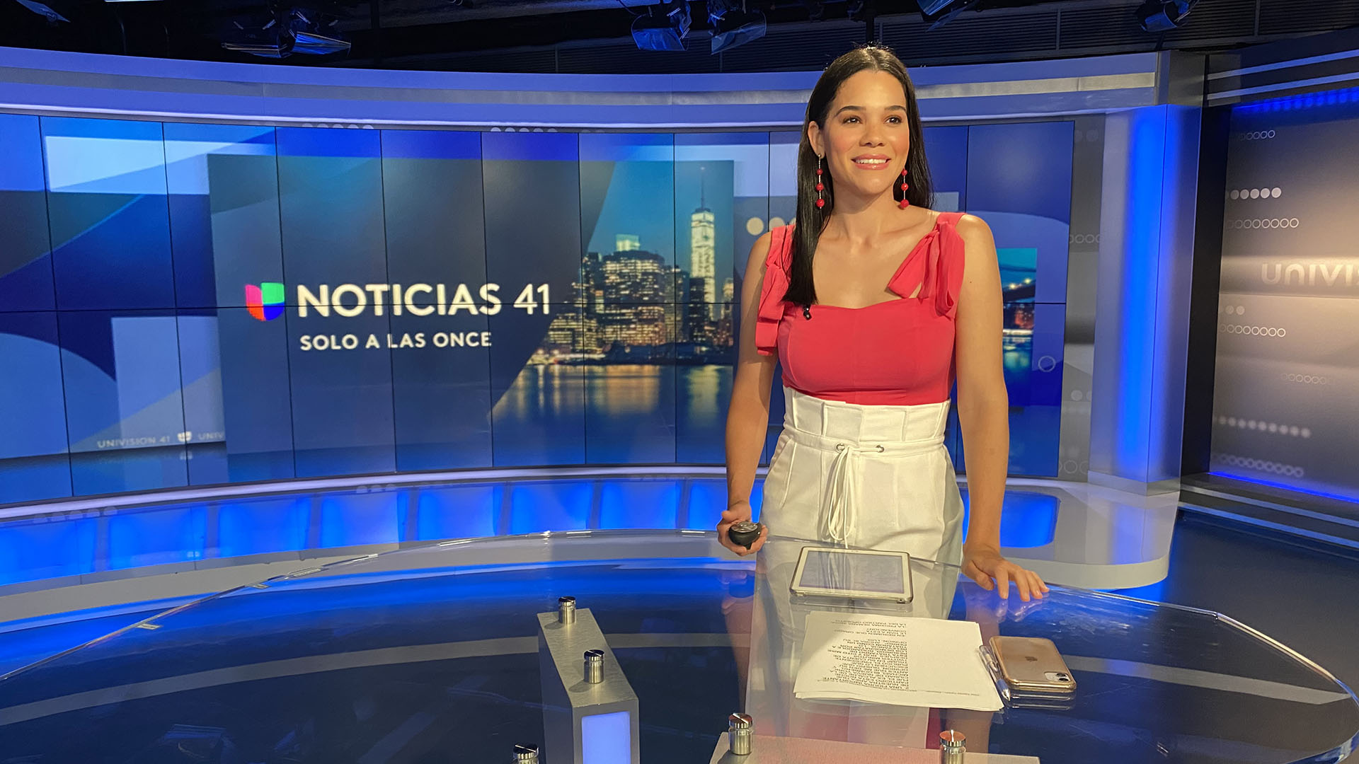 female anchor standing in front of news desk