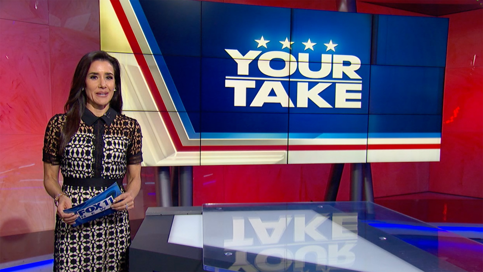 Female anchor standing next to screen with Your Take logo