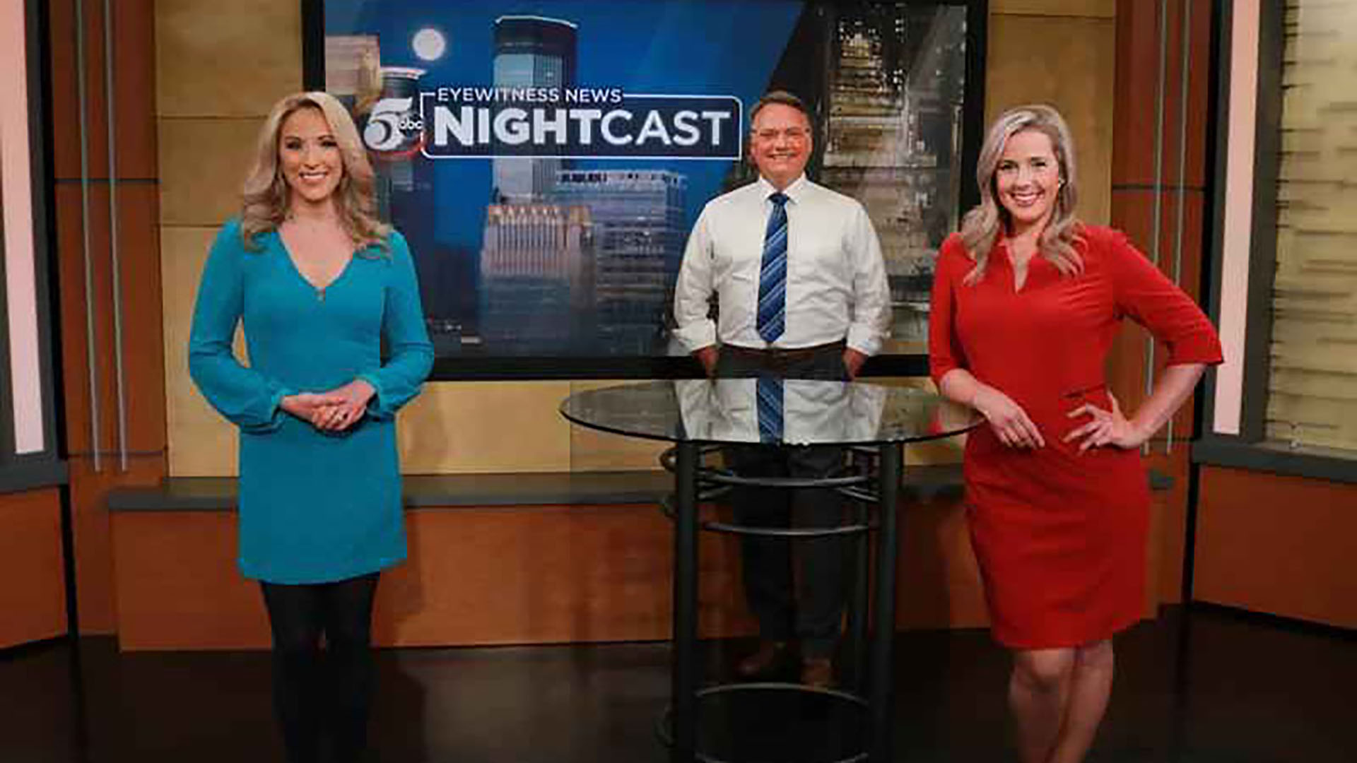 two female and one male news anchor standing by a table