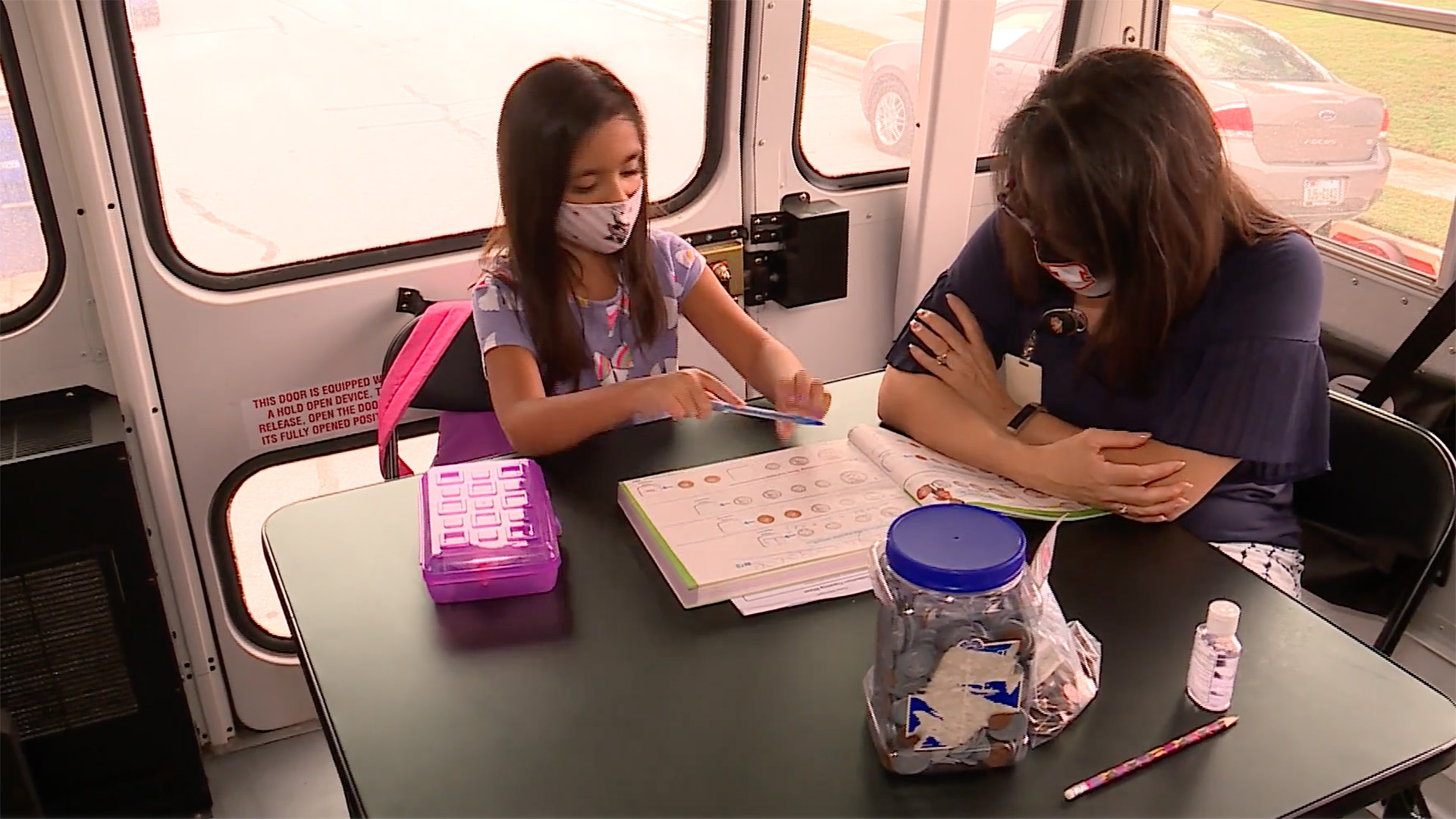 teacher and student with face masks on a school bus